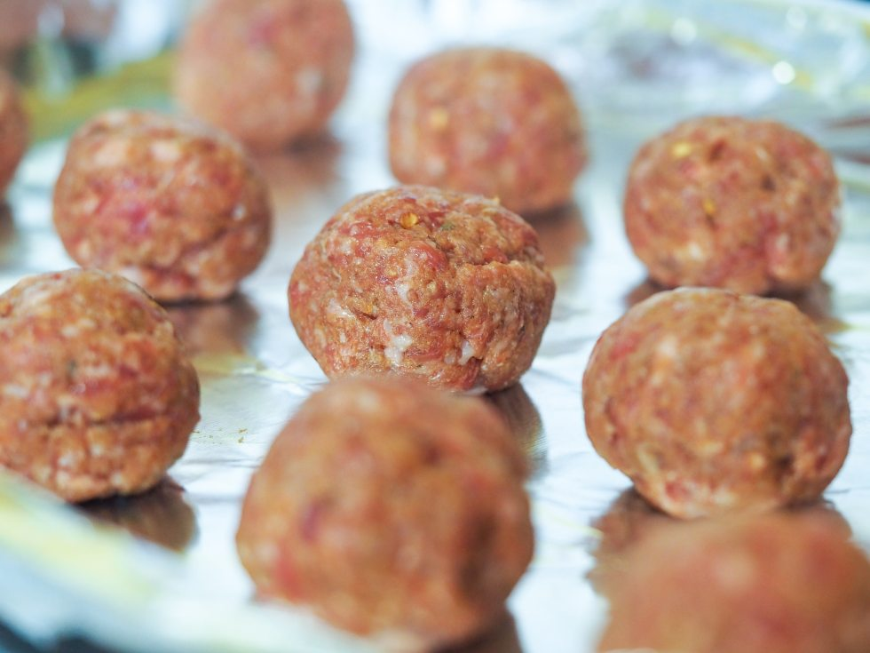 close up view of formed meatballs on cookie sheet