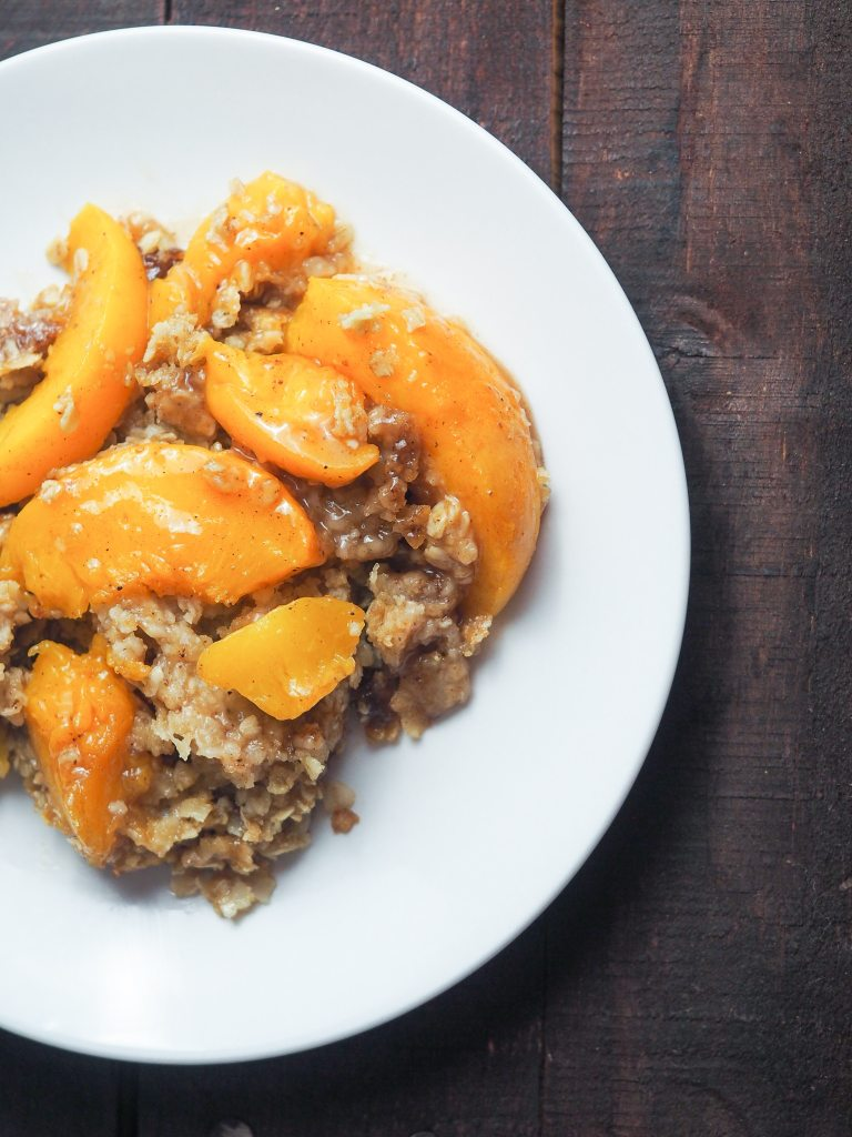 overhead view of peach crisp on white plate placed on a brown tabletop