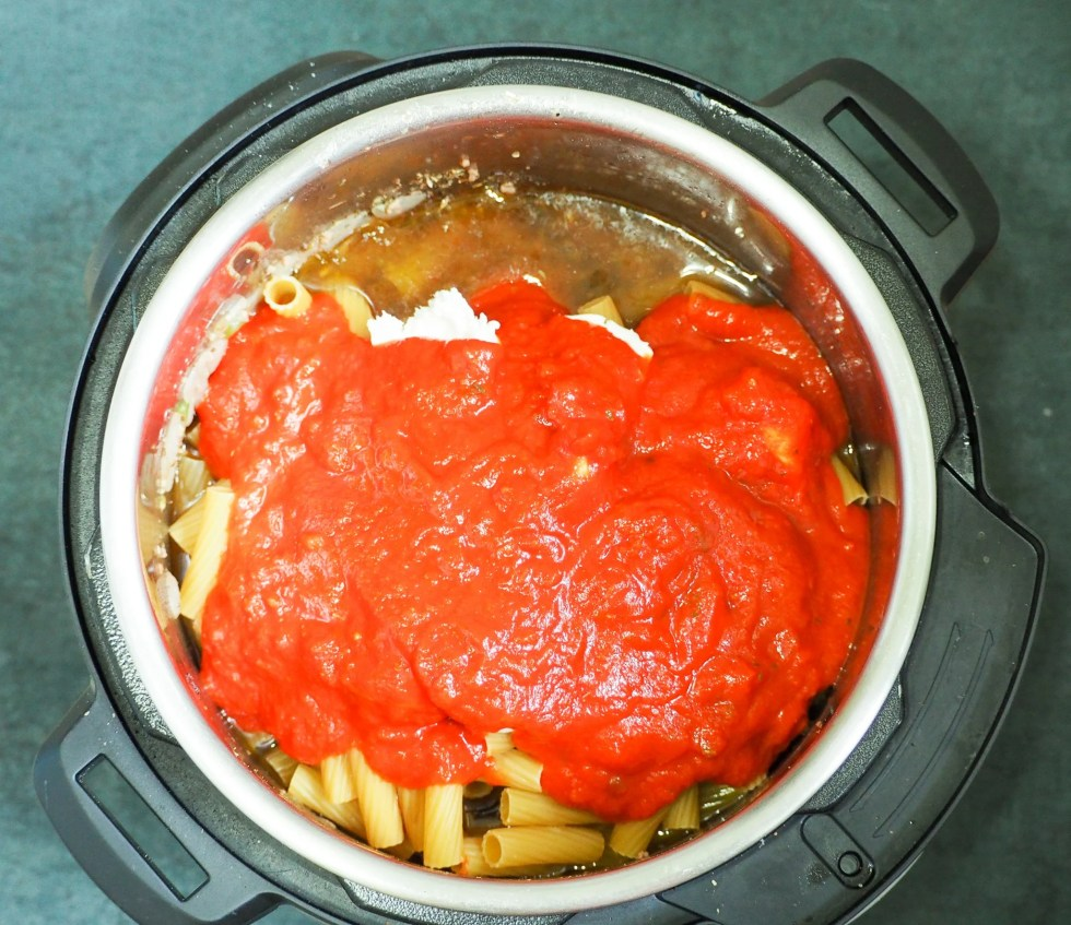 overhead view of ziti ingredients in instant pot topped with spaghetti sauce