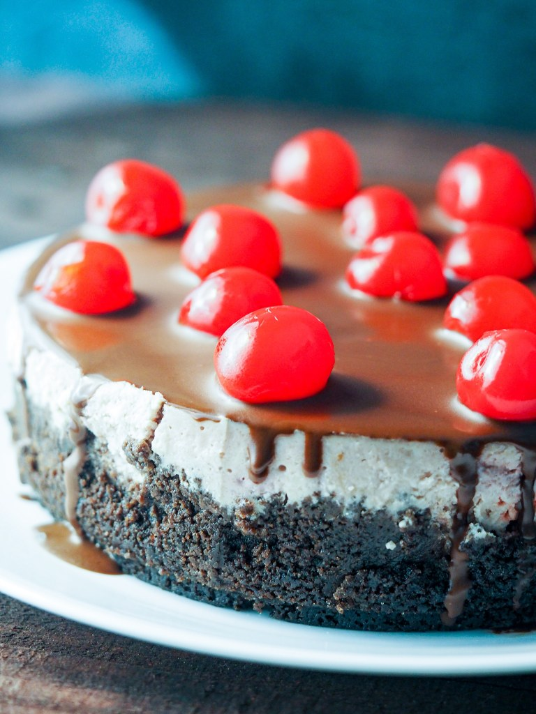 side view of cherry chocolate cheesecake on plate topped with maraschino cherries