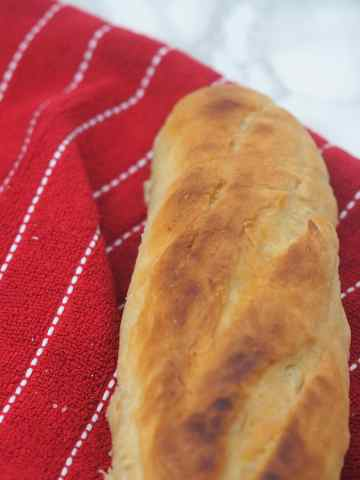 horizontal view of the top portion of a crusty french baguette sitting on a red towel with thin white stripes on a marble countertop