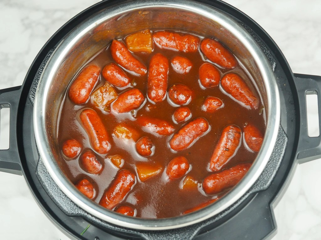 overhead shot of cooked little smokies in bbq sauce with pineapple in pressure cooker