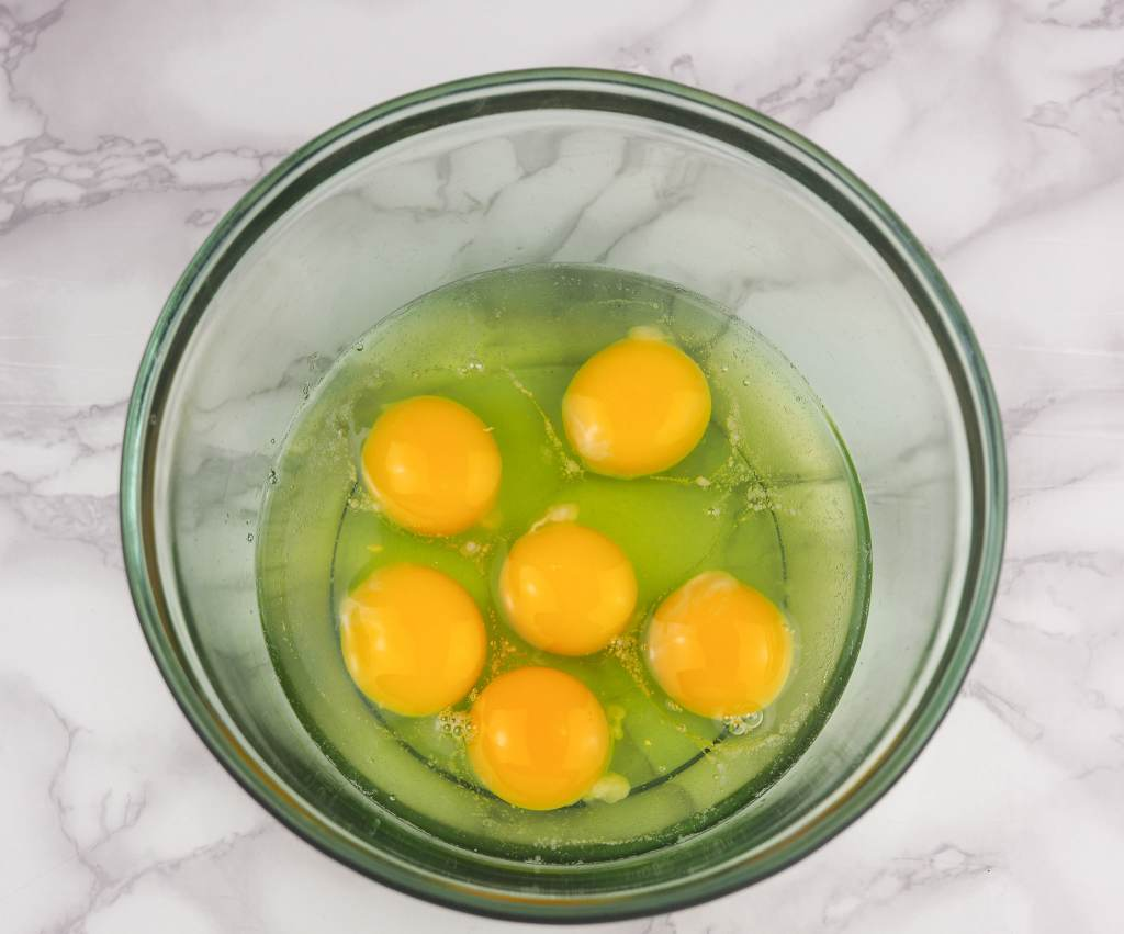overhead view of clear green glass bowl on counter top with six raw eggs inside