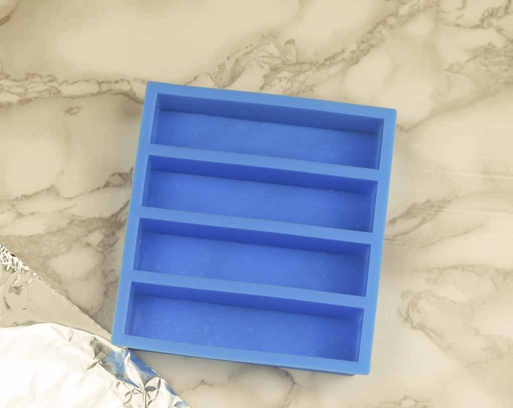 overhead view of siilcone ice cube stick tray with aluminum foil in bottom left corner