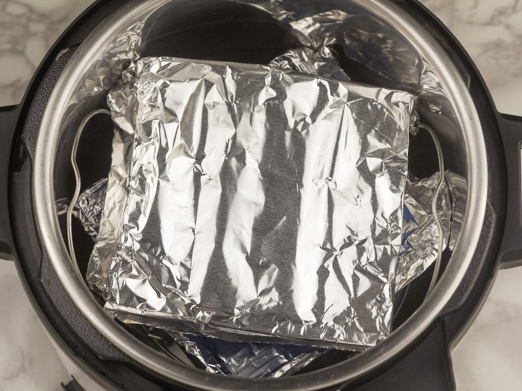overhead view of silicone trays covered with foil and stacked inside the instant pot