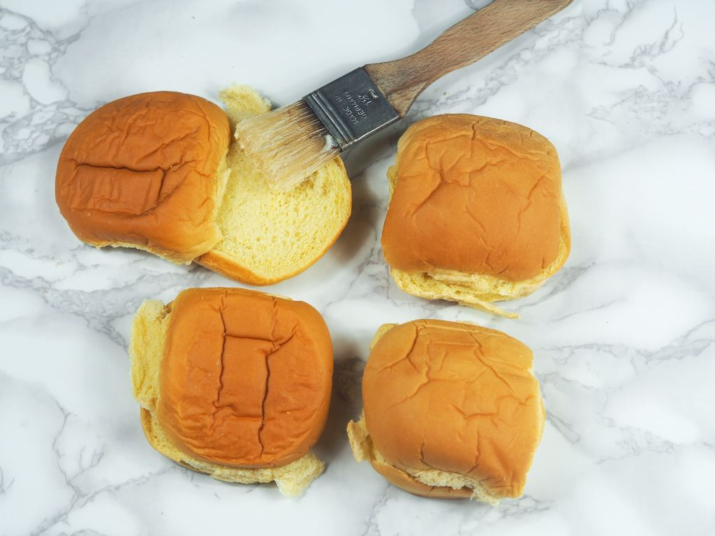 overhead shot of four hamburger buns on marble counter top with pastry brush with butter on it