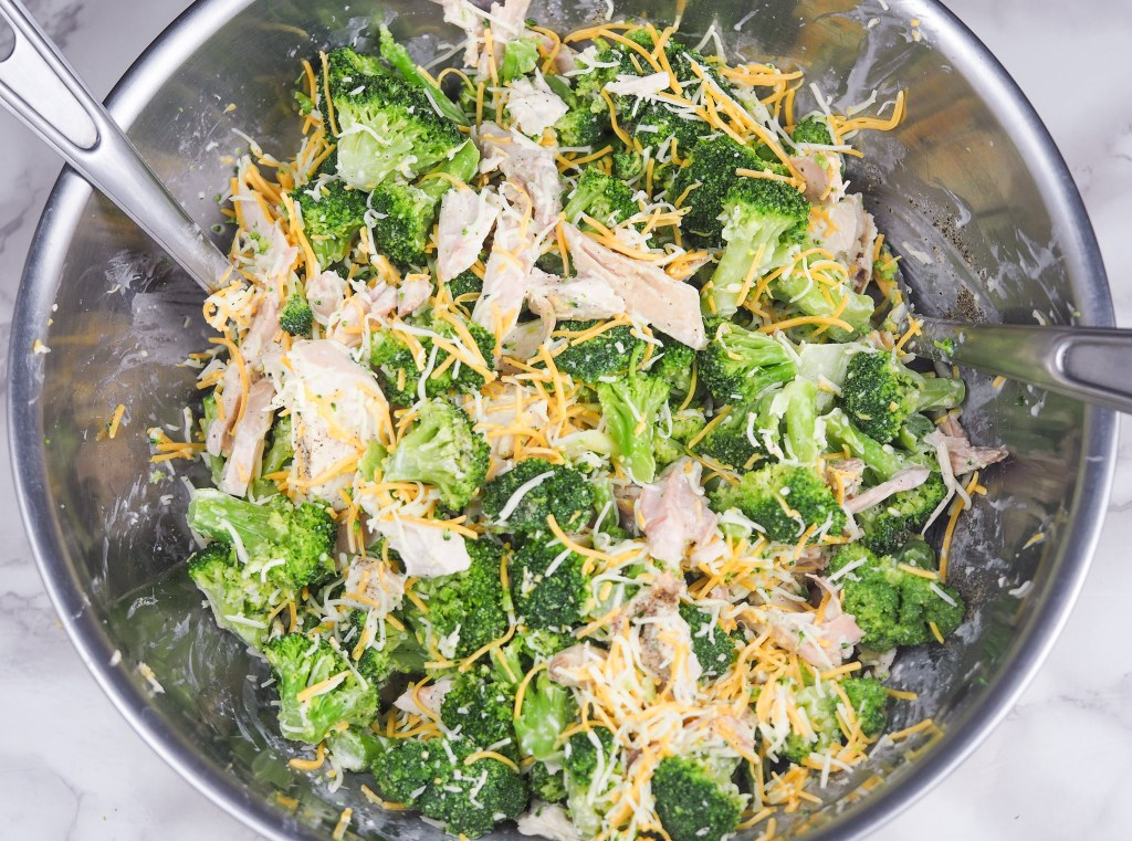 overhead view of raw broccoli chicken casserole in stainless steel bowl