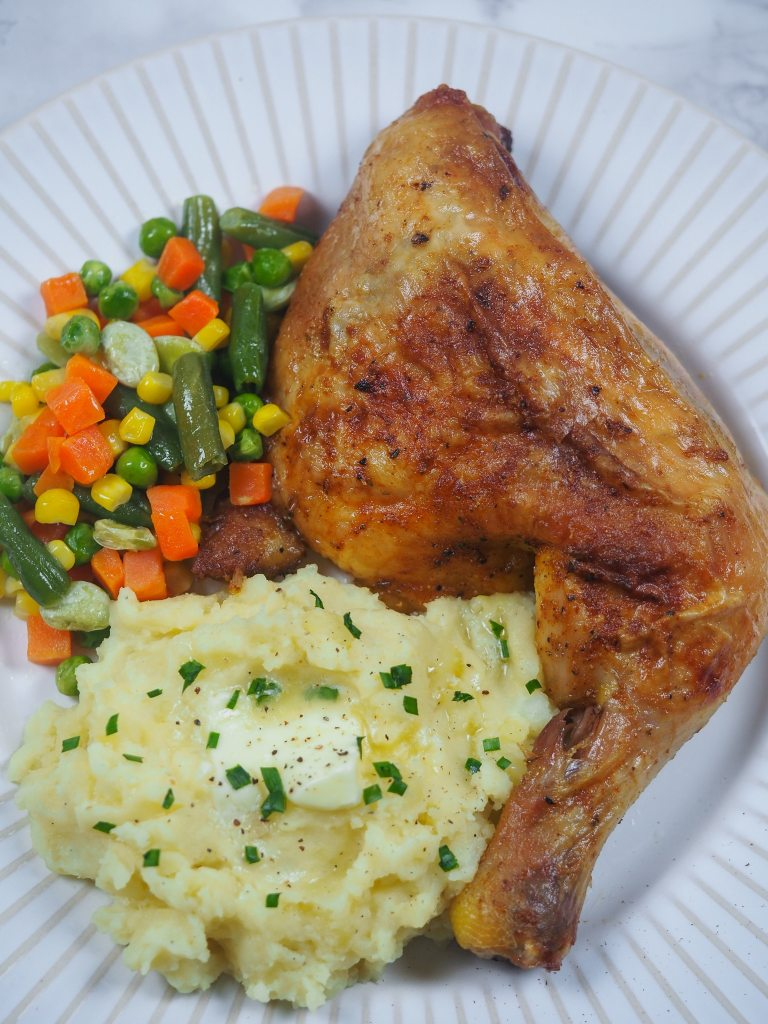 baked chicken leg quarter on white plate with mashed potatoes topped with butter and chives with mixed veggies on the side