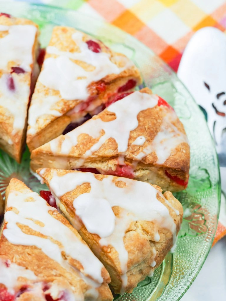 Vertical picture of cherry scones on clear glass decorative plate, view of half the plate with pie server in background on multi color napkin