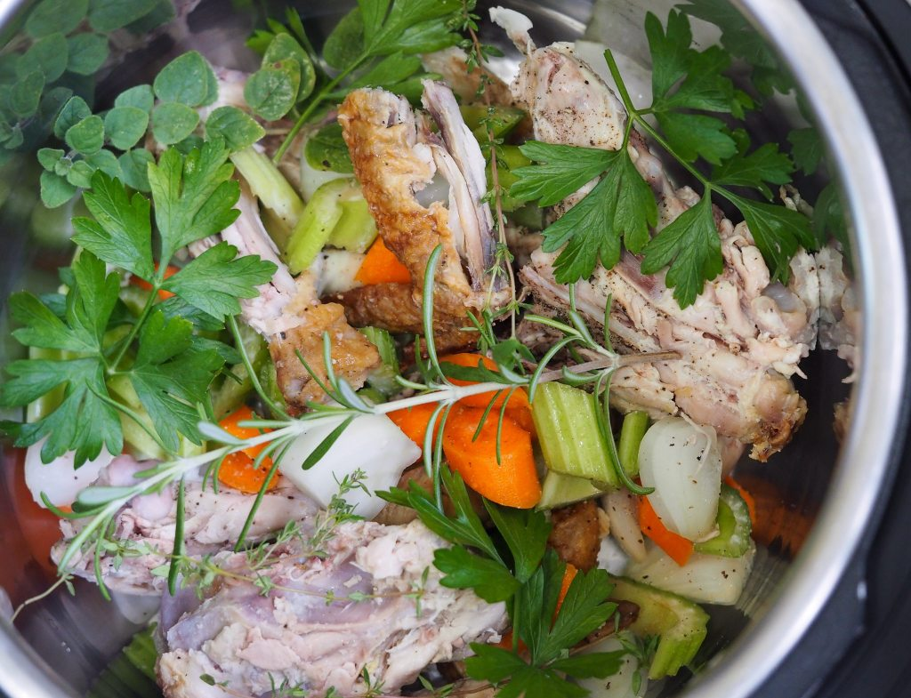 overhead view of cleaned chicken bones, but root vegetables, and fresh herbs in instant pot