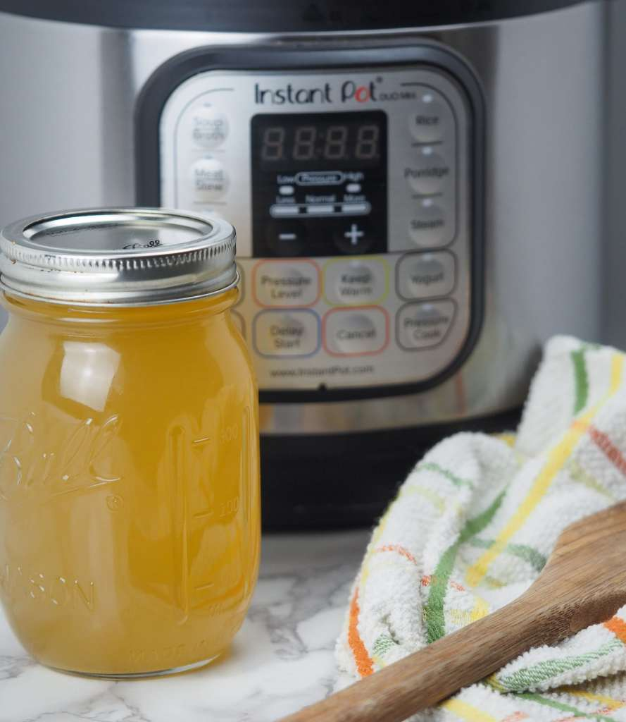 vertical image of pint canning jar filled with chicken bone broth next to kitchen towel and wooden spoon with pressure cooker in background