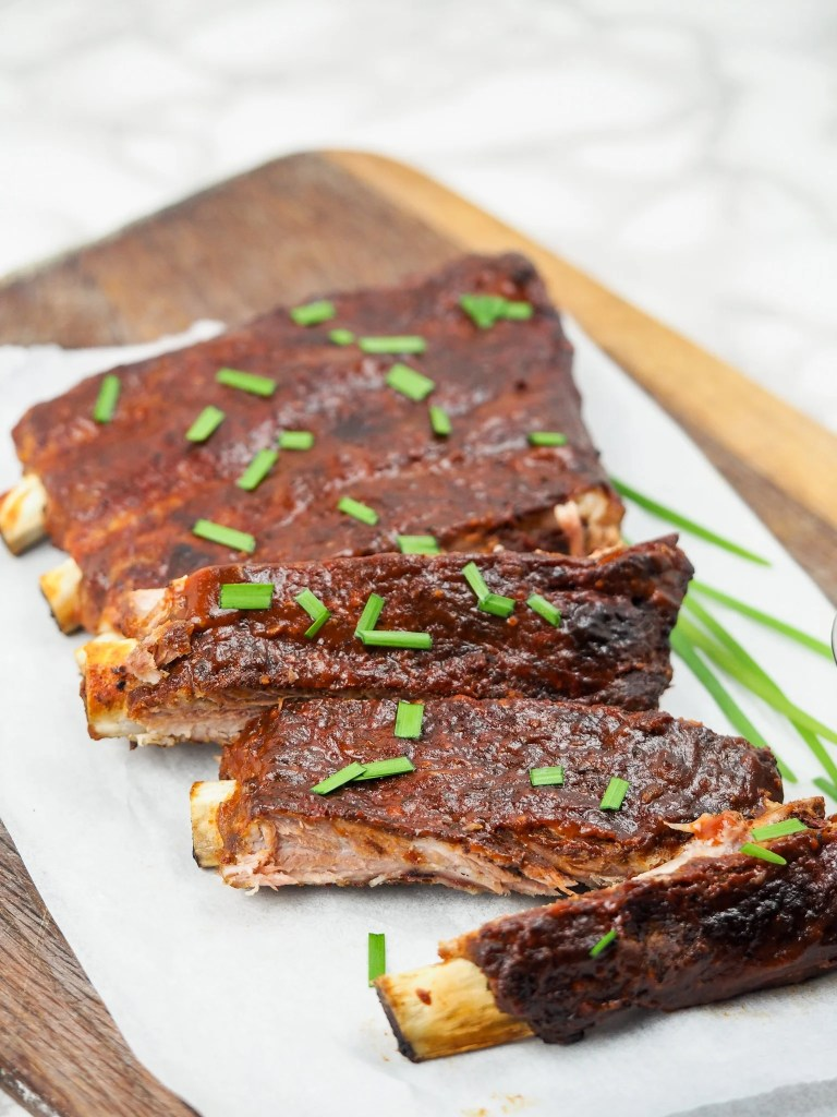 long vertical image of a rack of ribs on top of parchment paper on cutting board