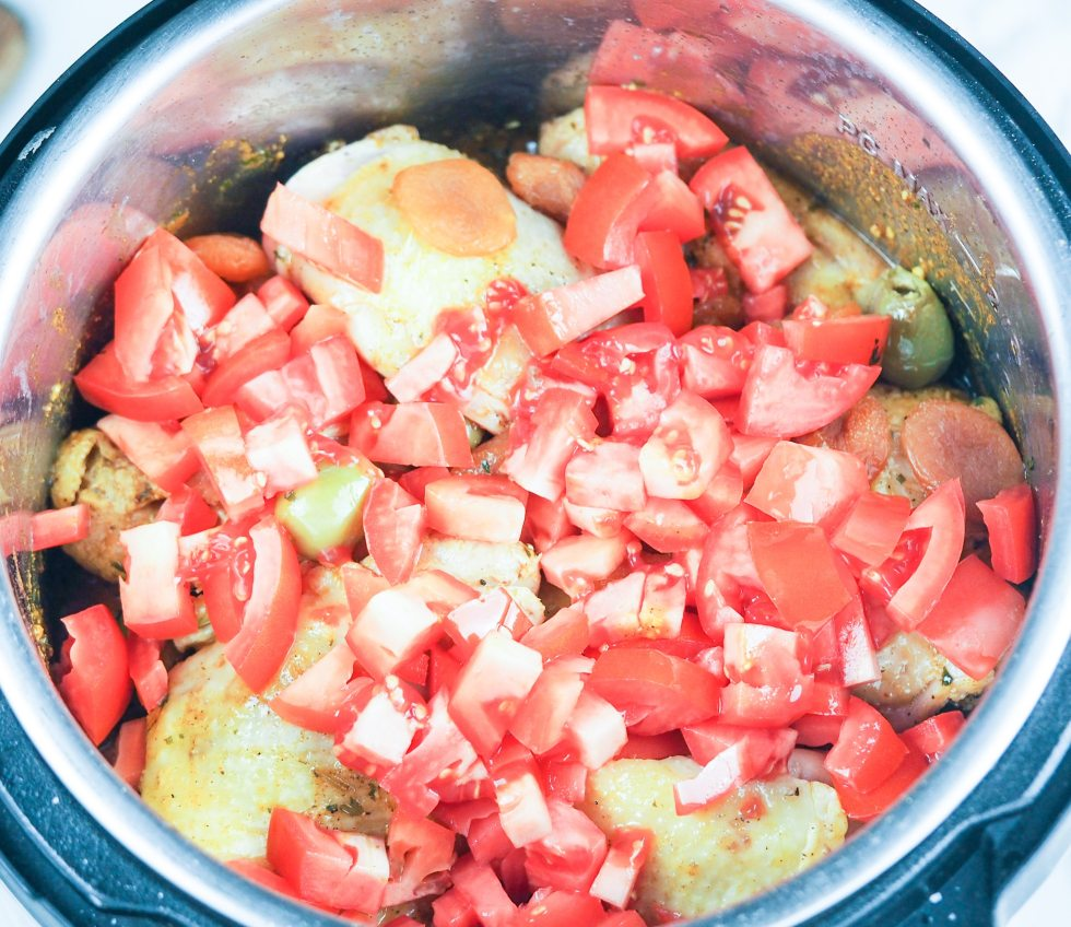 overhead view of chicken tagine ready to cook in the pressure cooker with all the ingredients layered