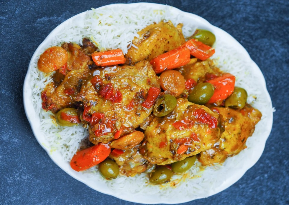 instant pot chicken tagine on black counter sitting on a bed of rice on white oval platter