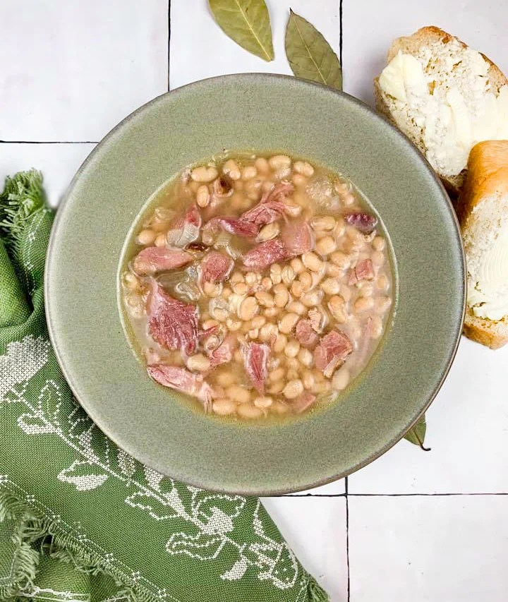 overhead view of navy bean soup in olive green bowl with green napkin at bottom left, sliced and buttered French bread at top right, on a tile surface with bay leaves scattered