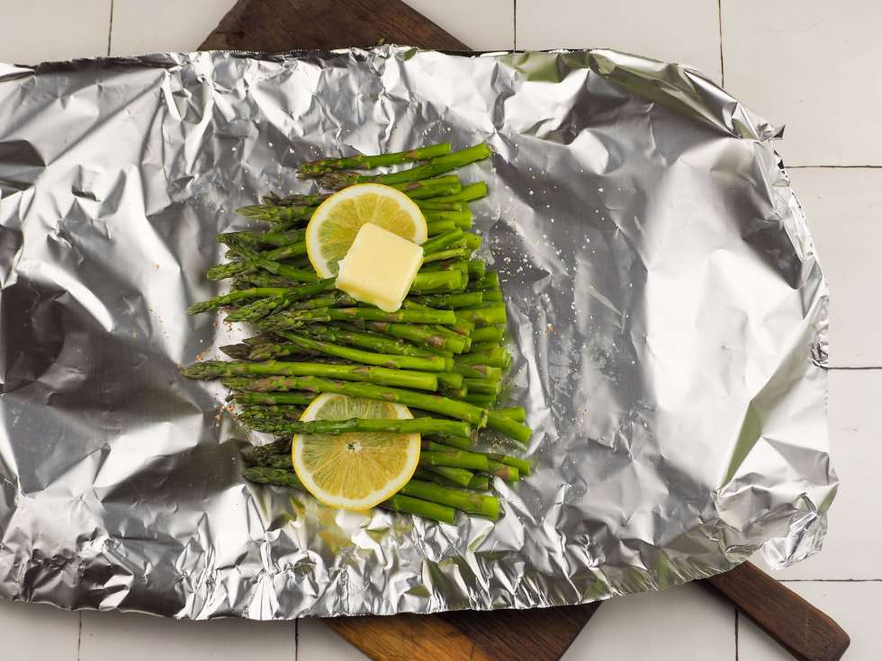 asparagus with lemon and butter on top of foil on cutting board