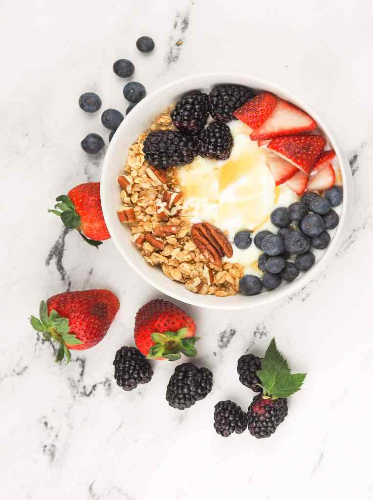 overhead view of finished yogurt bowl on marble countertop surrounded by fresh berries