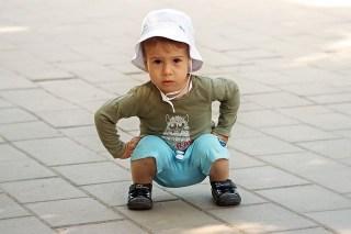 image d'un enfant accroupi comme une position de squat.