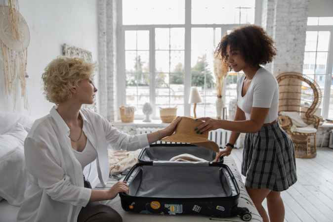 attractive women packing suitcase at home