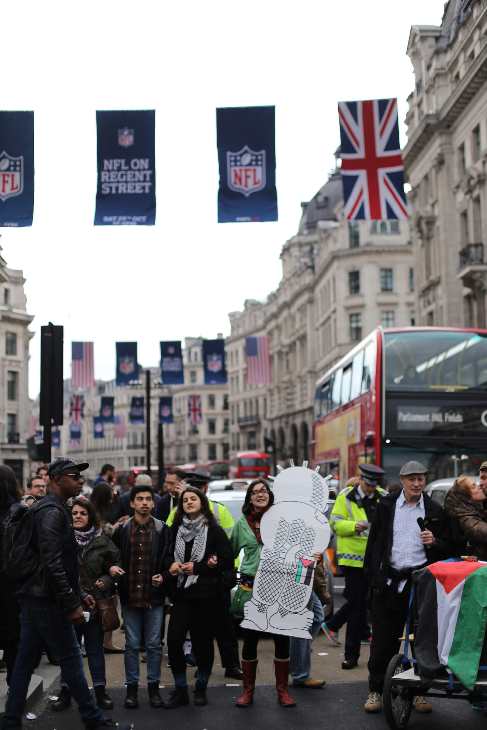 Protesters link arms stopping traffic on Oxford Street. Some hold representations of Handala, a creation of the late Palestinian cartoonist Nagi Al-Ali. Handala bears witness to the Israeli oppression of the Palestinian people. (Photo: Sara Anna)