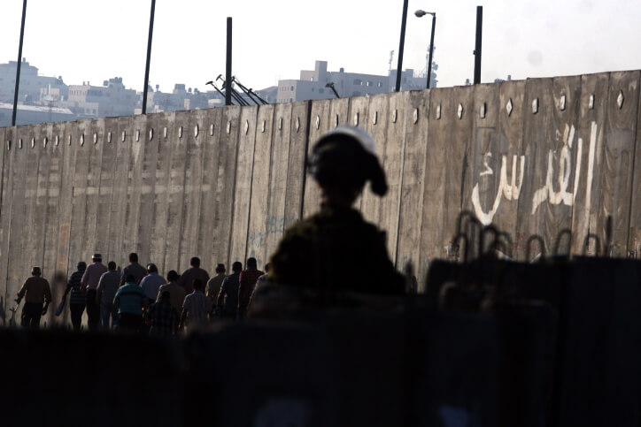 An Israeli soldier watches as Palestinians cross into Jerusalem from the Qalandiya checkpoint near the West Bank city of Ramallah. (Photo: Issam Rimawi/Flash90)