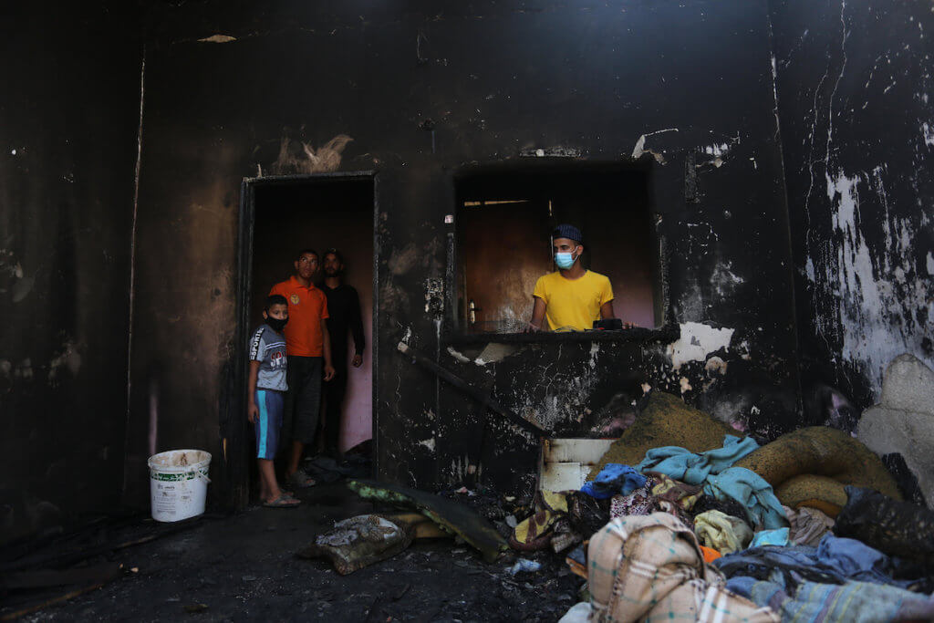 Palestinians check on a house that burned down in al-Nusirat refugee camp, taking the life of three children on September 2, 2020. The fire was started by a candle used to light up their room because no electricity was available due to power cuts. (Photo: Ashraf Amra/APA Images)