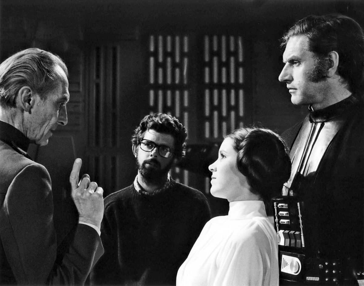 The late Peter Cushing, George Lucas, the late Carrie Fisher and the late David Prowse on the set of 'Star Wars.'