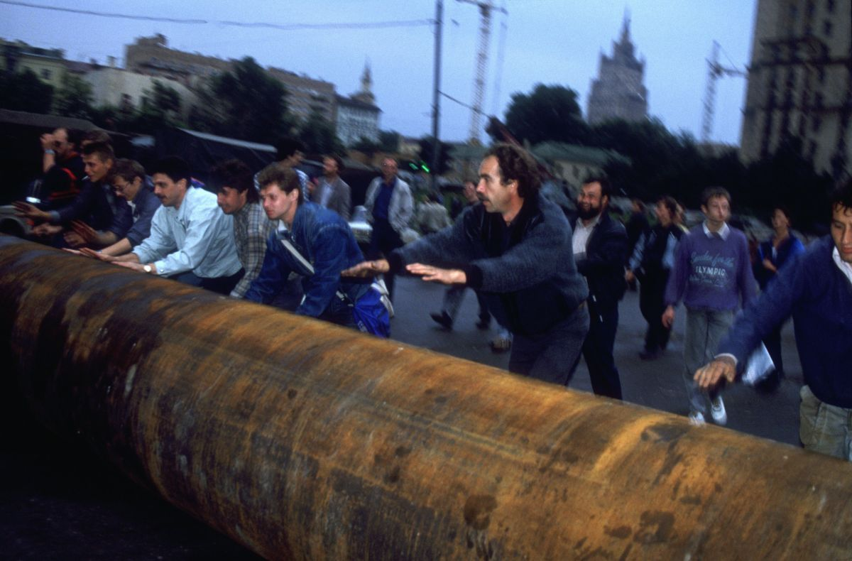 Demonstrators roll a large metal pipe through the streets of Moscow to help form a barricade outside the Russian White House.