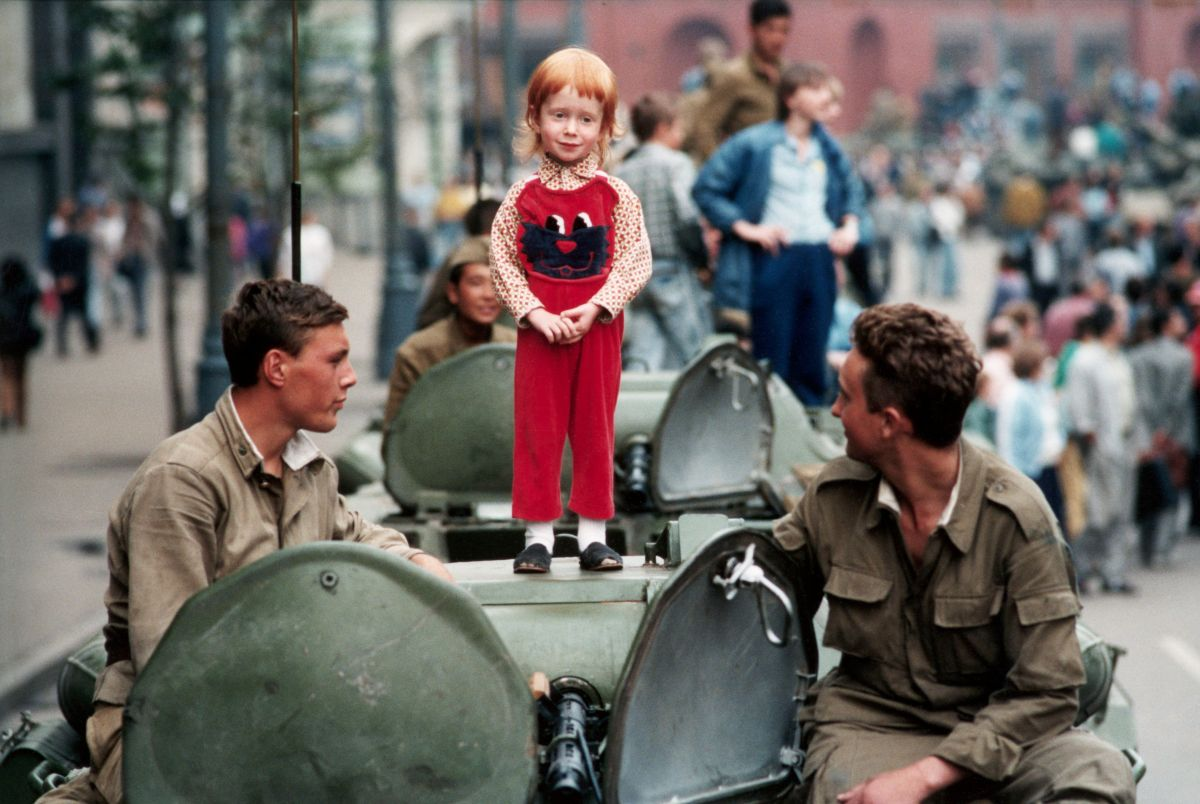 A little girl stands placidly atop a Soviet tank in the barricades at Red Square during the coup.