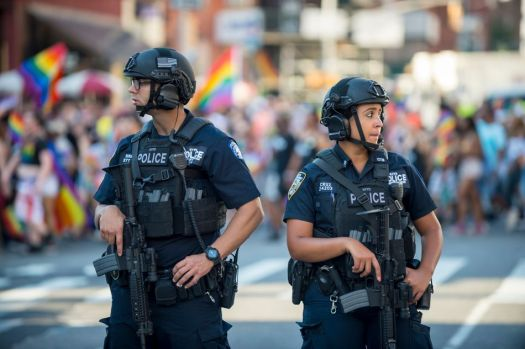 NYPD police officers stand with hands on their weapons, providing security on the sidelines of the annual New York Pride parade as it passes through Greenwich Village in 2017.