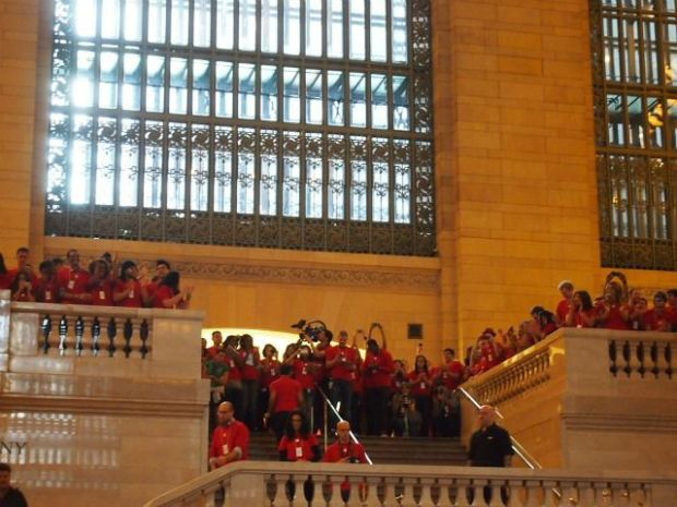 Apple employees clad in red holiday shirts cheered from the store's balconies, which overlooks Grand Central's main concourse.