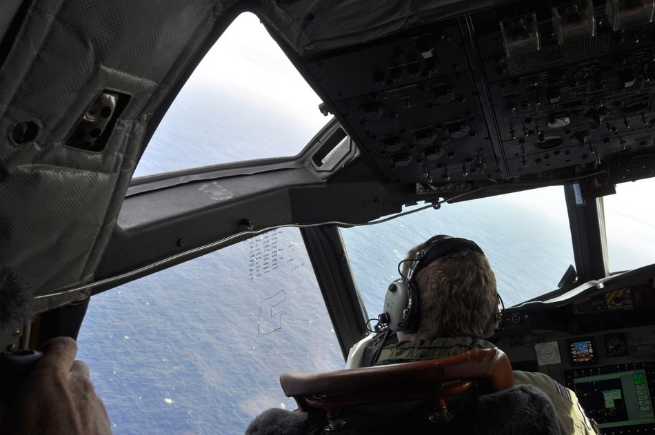 A crewman on a Royal New Zealand Air Force P-3 Orion Rescue Flight 795 searches for debris from the missing Malaysia Airlines Flight MH370 on April 1.