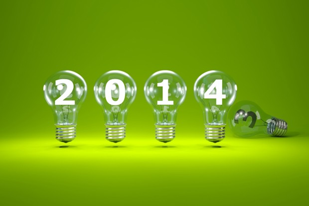 2014 New Year sign inside light bulbs on green background