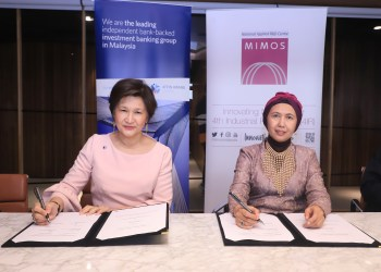 Datuk Maimoonah Hussain, Group Managing Director, Affin Hwang Capital (left) and Pn.Emelia Matrahah, Interim President and CEO, MIMOS Berhad (right) signing the document to signify the strategic collaboration