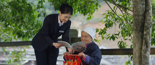 Photo shows an employee of Guilin Bank explains the rural vitalization policies to a villager in rural area of Guangxi. (By Jiang Chen)
