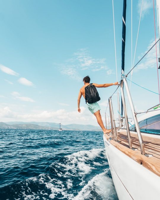 man wearing backpack standing on side of boat during daytime