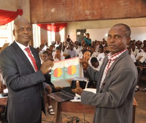 l-r: Executive Director, Lagos and West Bank, Marketing, United Bank for Africa, Liadi Ayoku donating books and other gift items  to the Vice Principal, Academic, Olivet Baptist High School, Oyo, Oyo State, Mr. E.A Adedeji,  during the financial literacy training programme for students of the school, an  initiative of Central Bank of Nigeria, in commemoration of World Savings Day on Monday in Oyo, Oyo State