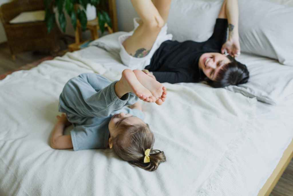 cheerful young mother with little child having fun on bed