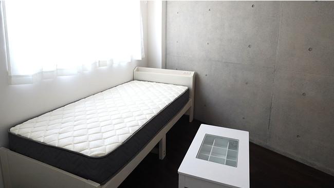 室内壁はコンクリート打ち放しによるデザイン性の高い内装、ベッド・テーブルの一部家具付き