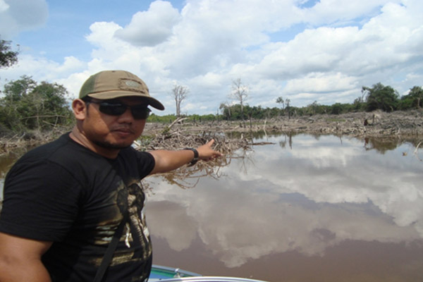 Rayendra, Chairman of theSintang Fishing Club, shows Lake Jentawang near Nanga Ketungau Village, which has allegedly been damaged by waste from palm oil companies. Photo: Yusrizal