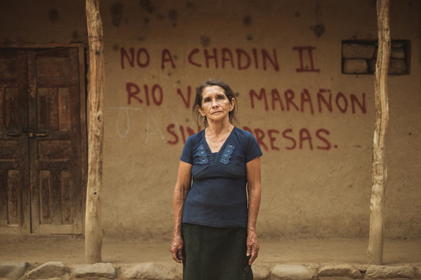 Local resident Juana stands in front of graffiti protesting the Chadin 2 dam. Photo credit: David Hill.