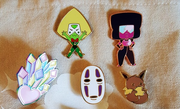 Starting an Art Business. Group of 5 enamel pins displayed on a canvas tote bag. Top row has two Steven Universe pins (Peridot and Garnet), while the second has a heart with crystals coming out of it, No Face from Spirited Away, and an Eevee (Pokemon).