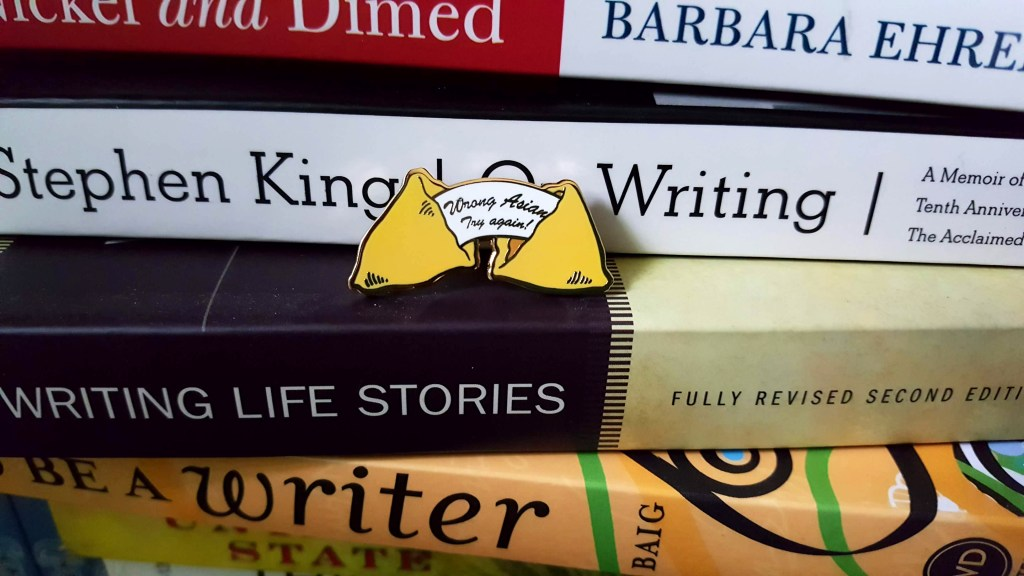 "Wrong Asian pin set on a pile of books including ""On Writing"" by Stephen King, ""Nickel and Dimed"" by Barbara Ehrenreich, and ""Writing Life Stories"""