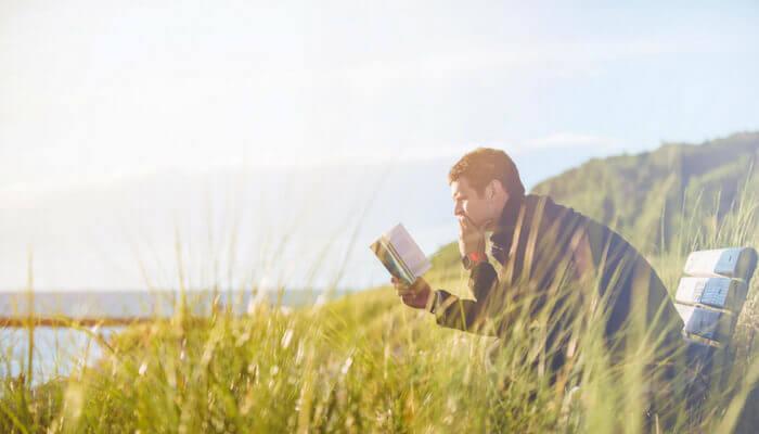 Stress bewältigen, Mann sitzt auf Bank und liest in einem Buch