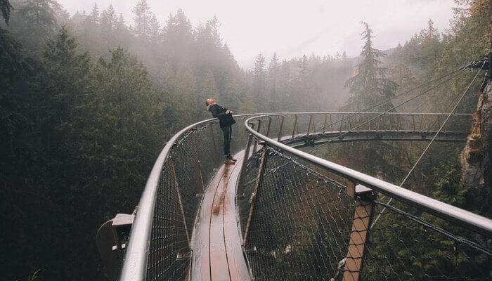 Höhenangst Therapie, Hängebrücke mann lehnt sich ans Geländer