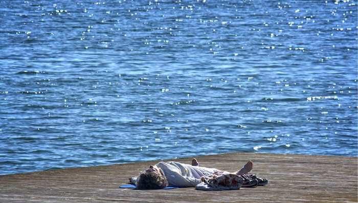Mittel gegen Stress, Mann liegt auf einem Steg am Wasser