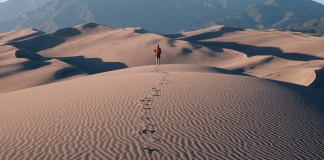 Lonely Man walking in desert leaving footprints in sand