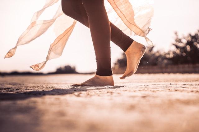 inquadratura dal ginocchio in giù di una persona che cammina sulla sabbia a piedi nudi. Indossa un paio di leggings lunghi e probabilmente un gonnellino di stoffa trasparente con numerose punte che toccano quasi terra.