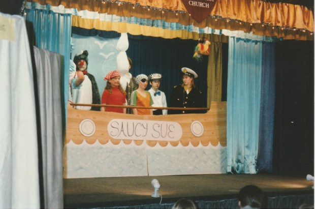 Characters from Dick Whittington on stage, in a boat called Saucy Sue