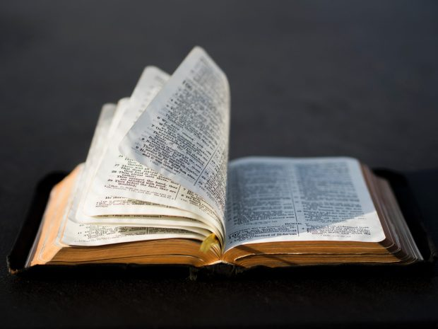 An open Bible with pages turning in the wind